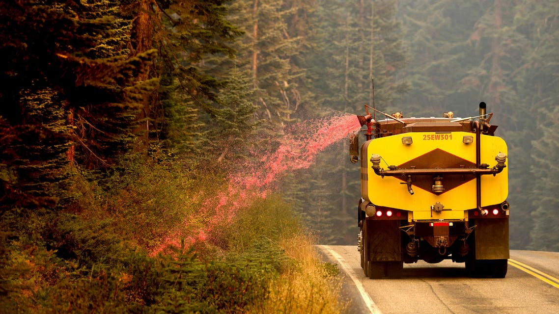 A truck sprays fire retardant on vegetation to help stop the spread of the North Complex Fire in Plumas National Forest, Calif., on Monday, Sept. 14, 2020. (AP Photo/Noah Berger)