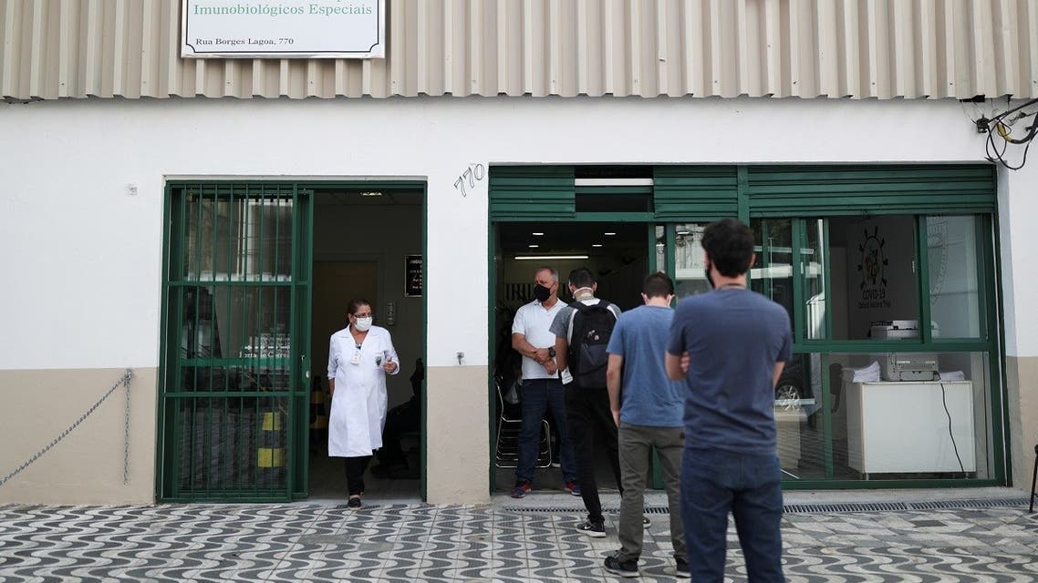People stand in front of the Reference Center for Special Immunobiologicals where the trials of the Oxford/AstraZeneca coronavirus vaccine are conducted, Sao Paulo, Brazil, June 24, 2020. (Reuters)