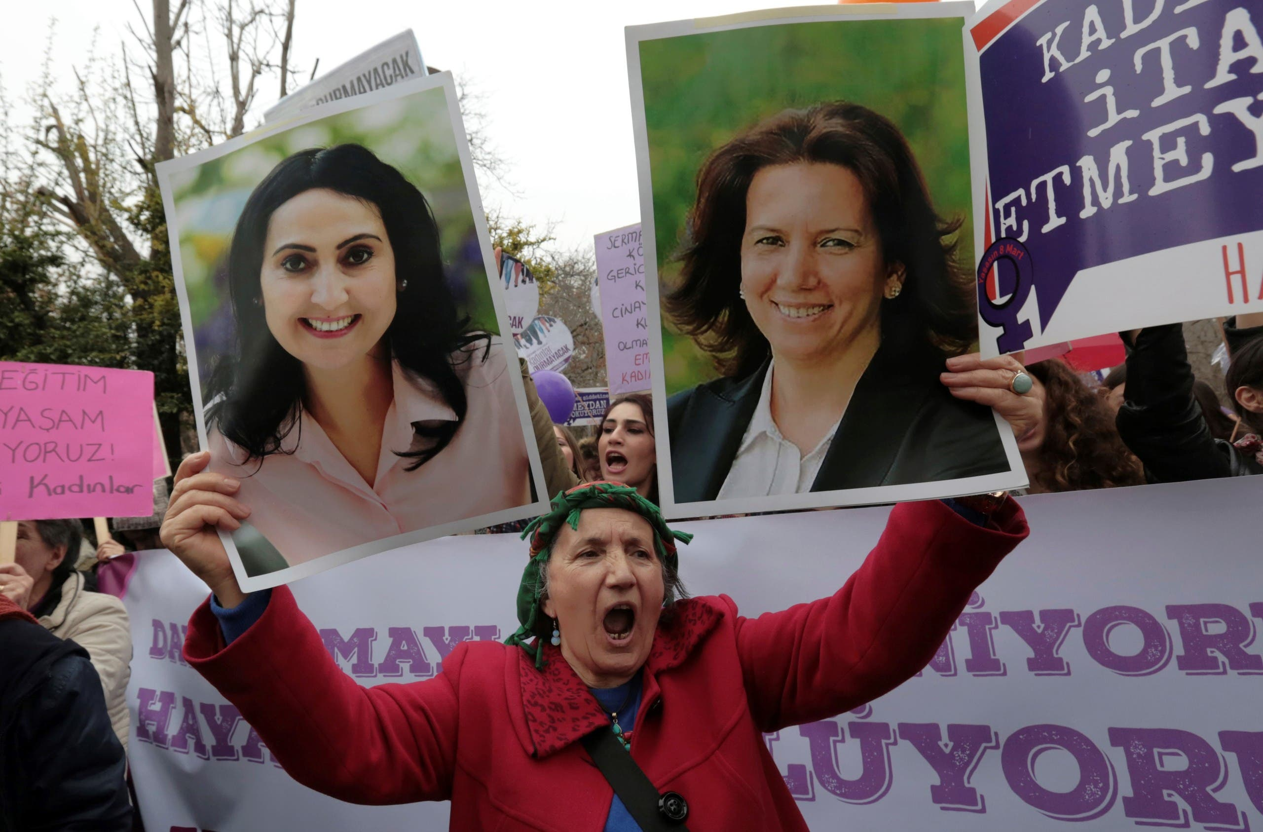 A woman holds images of imprisoned pro-Kurdish lawmakers Figen Yuksekdag, left, who was charged with insulting the president, and Selma Irmak in Ankara. (File photo: AP)