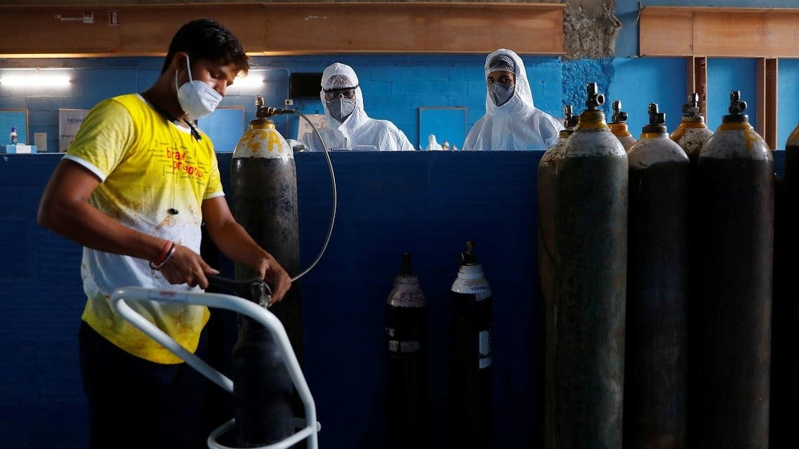 A worker refills an oxygen cylinder as medical workers wait at the Yatharth Hospital in Noida, on the outskirts of New Delhi, India, on September 15, 2020.  (Reuters)