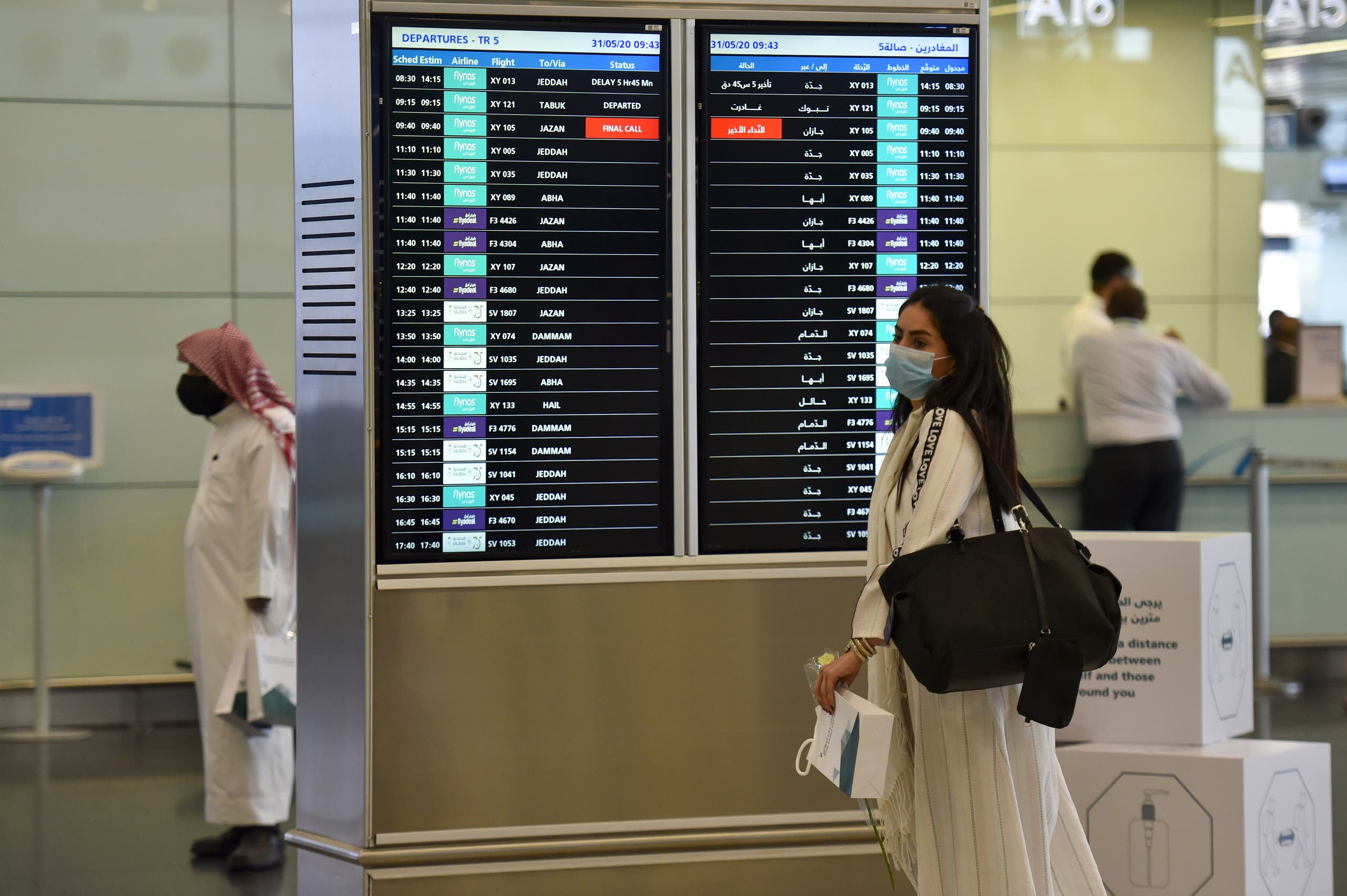 A Saudi passenger, wearing a protective face mask, arrives at terminal 5 in the King Fahad International Airport. (AFP)