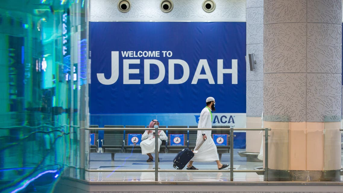 a traveller, mask-clad due to the COVID-19 coronavirus pandemic, walking with his luggage as part of the first group of arrivals for the annual Hajj pilgrimage, at the Red Sea coastal city of Jeddah's King Abdulaziz International Airport. (AFP)
