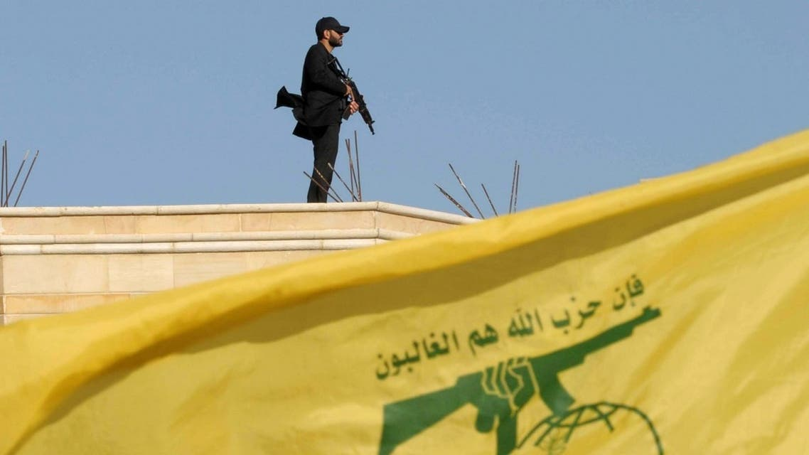 A Hezbollah member carries his weapon on top of a building as Lebanon's Hezbollah leader Sayyed Hassan Nasrallah appears on a screen during a live broadcast. (File photo: Reuters)