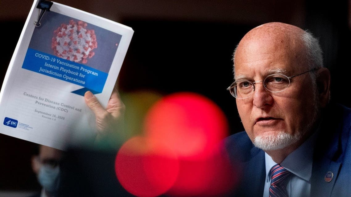 Centers for Disease Control and Prevention Director Dr. Robert Redfield holds up a CDC document that reads COVID-19 Vaccination Program Interim Playbook for Jurisdiction Operations. (Reuters)
