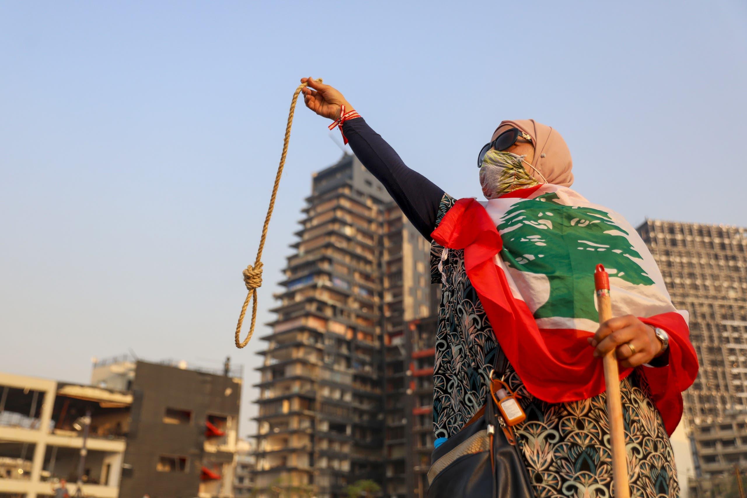 متظاهرة في لبنان تدعو لمحاسبة المتورطين في انفجار مرفأ بيروت حاملة حبل مشنقة (أرشيفية- فرانس برس)