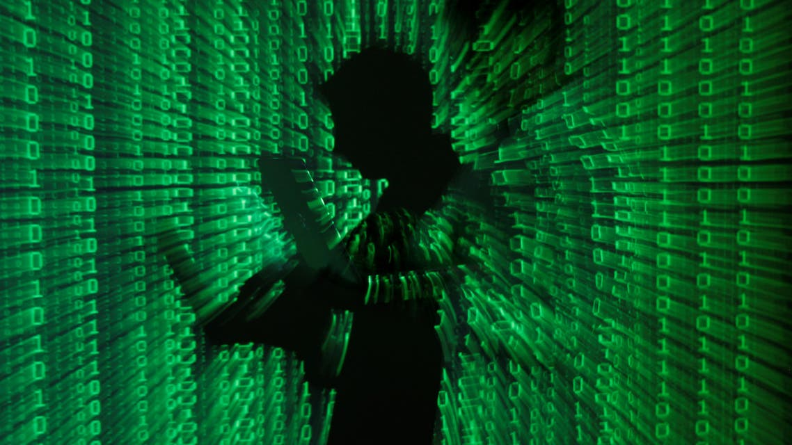 An illustration picture shows a projection of binary code on a man holding a laptop computer, in an office in Warsaw. (File photo: Reuters)