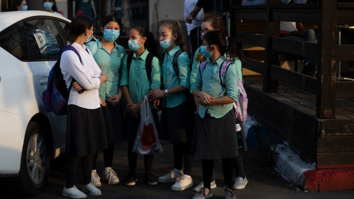 Ultra-Orthodox school girls wearing face masks amid the coronavirus pandemic wait to cross a street in Beit Shemes, Israel, Tuesday, Sept. 8, 2020. (AP)