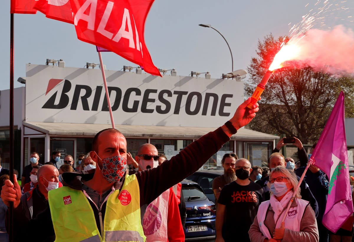 A CGT labour union member, wearing a protective face mask, holds a red flare during a protest with workers in front of the Bridgestone's tyre plant in Bethune, that Japan's Bridgestone plans to shut, France, on September 17, 2020. (Reuters)