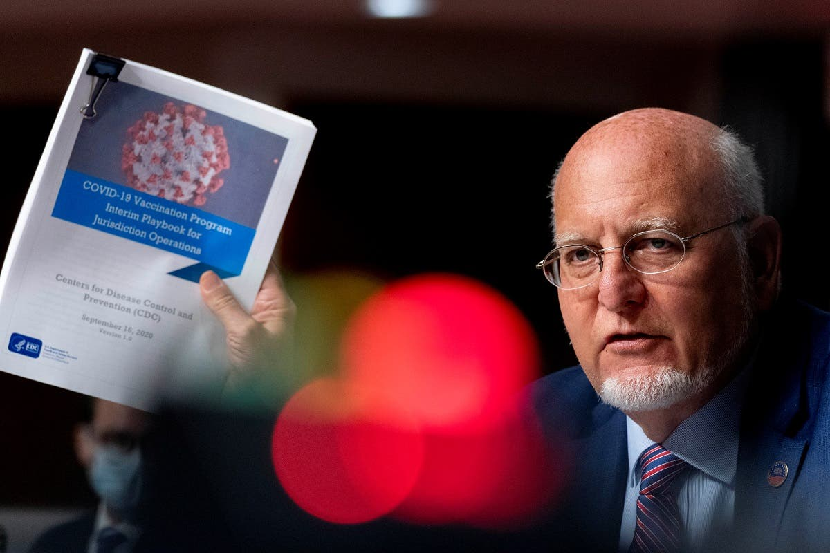 CDC Director Dr. Robert Redfield holds up a CDC document at a Senate Appropriations Subcommittee hearing, Sept. 16, 2020. (Reuters)