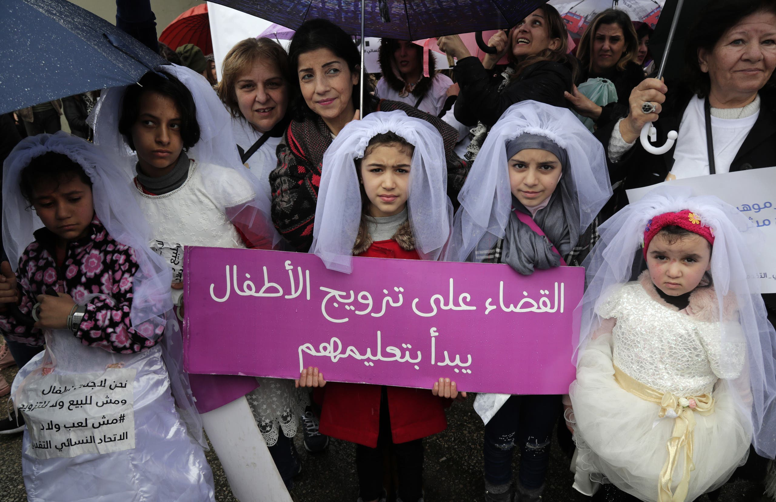 Young Lebanese girls disguised as brides hold a placard as they participate in a march against marriage before the age of 18, in the capital Beirut on March 2, 2019. (AFP)