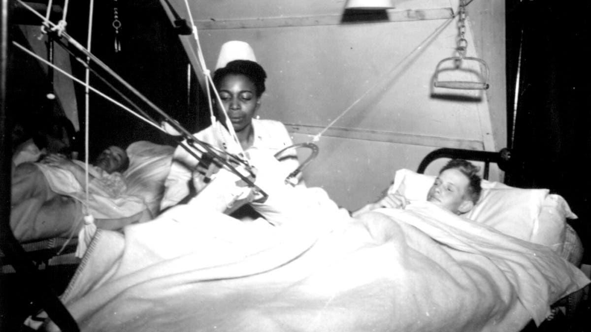 صورة لممرضة أميركية من السود أثناء اعتنائها بأسير ألماني