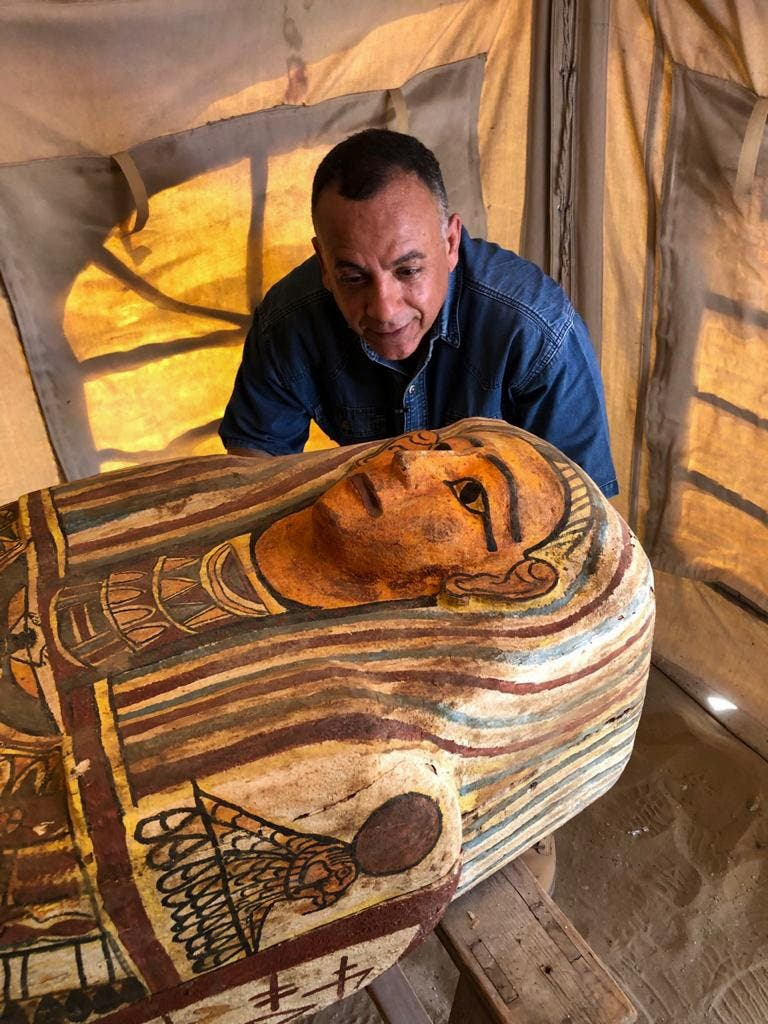 A handout picture released by Egypt's Ministry of Antiquities on September 20, 2020, shows Secretary General of the Supreme Council of Antiquities Mostafa Waziri (C) inspecting one of fourteen coffins discovered in Saqqara. (AFP)