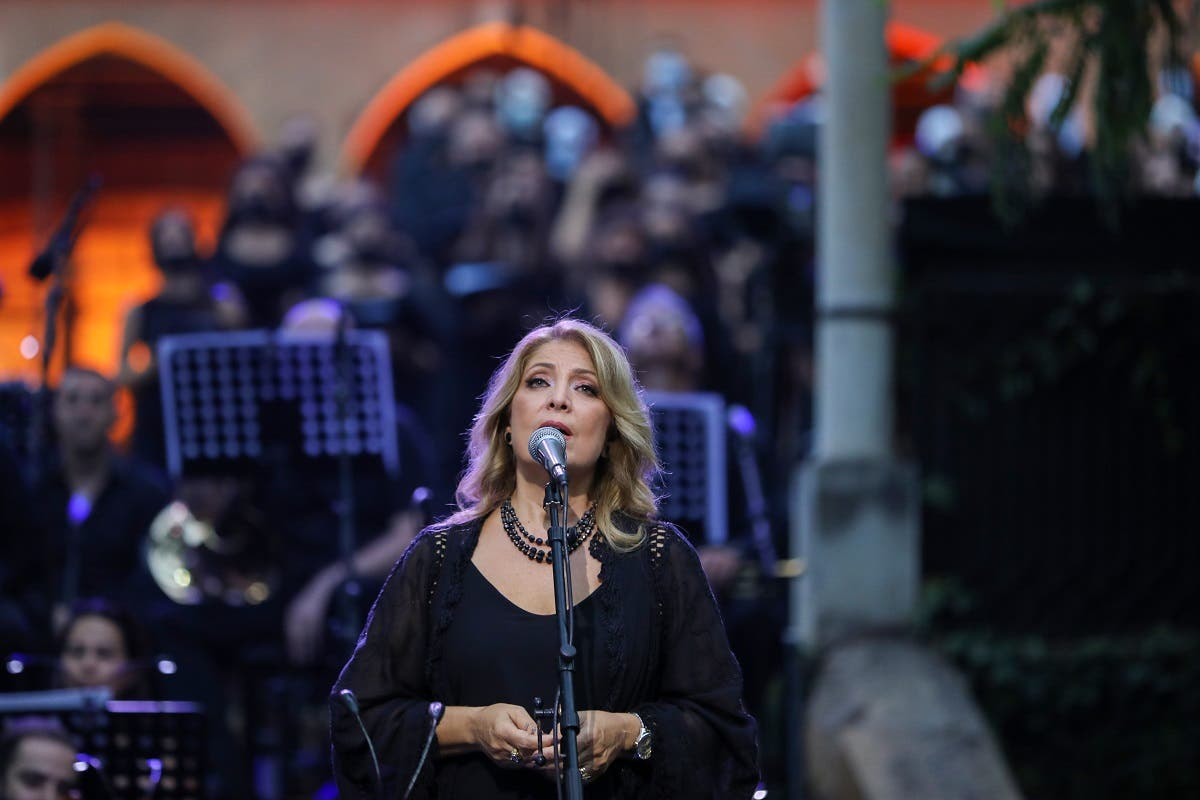 Lebanese singer Fadia Tomb El-Hage performs with a choir at a concert for the victims of August's deadly Beirut blast, in the gardens of the damaged 19th-century Sursock Palace in Achrafieh in Lebanon's capital, on September 20, 2020. (AFP)