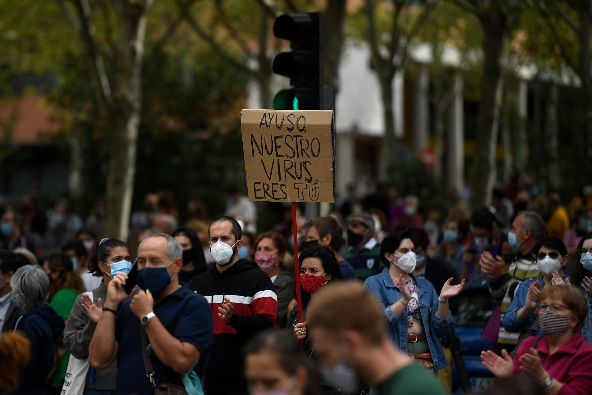 "A woman holds a placard reading ""Ayuso you are our virus"" during a demonstration at the Vallecas neighborhood in Madrid, on September 20, 2020. (AFP)"