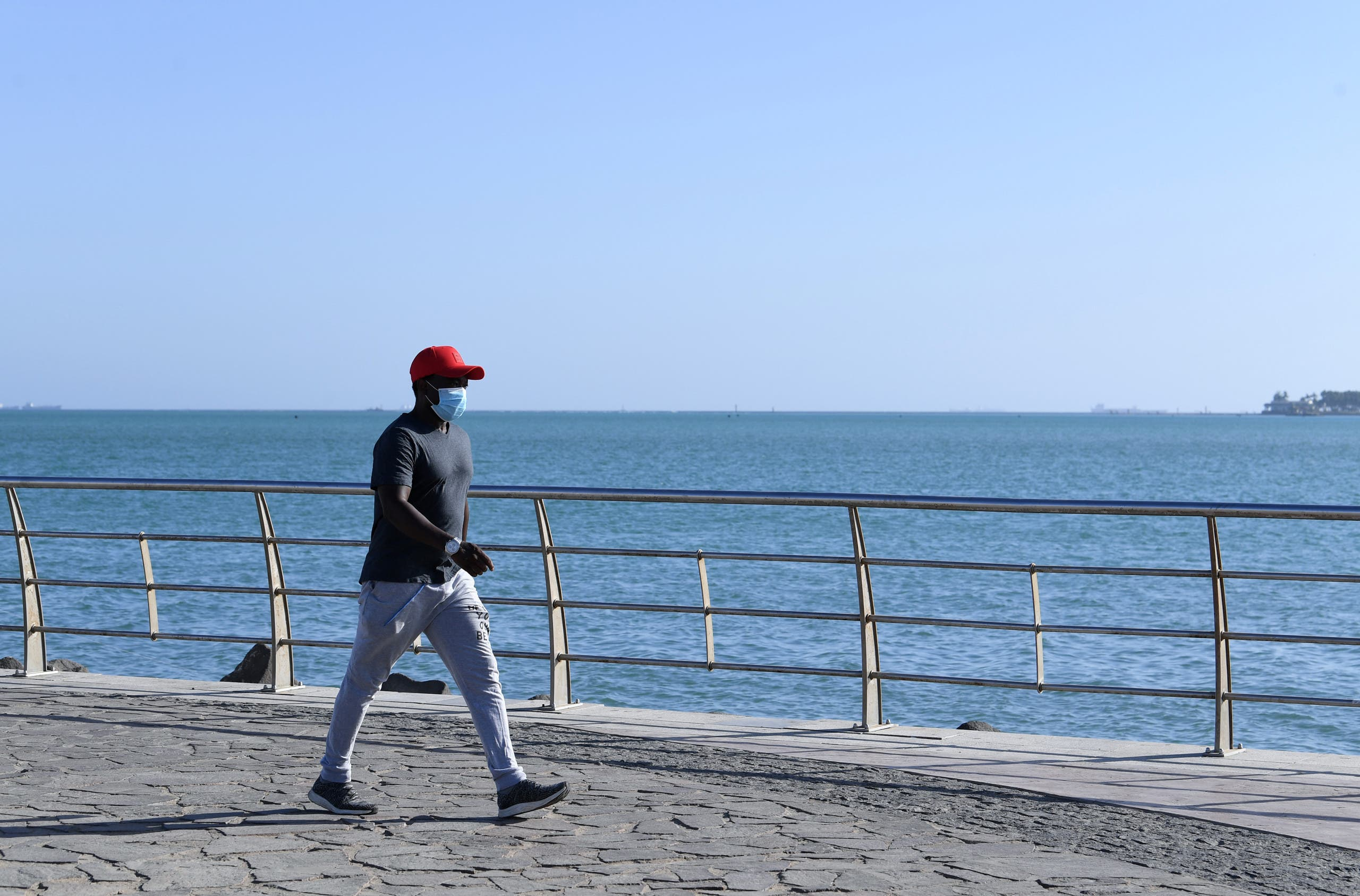 A man walks at the seafront promenade in the Saudi seaport of jeddah, on June 21, 2020, as the country re-opens following the lifting of a lockdown due to the COVID-19 pandemic. (AFP)