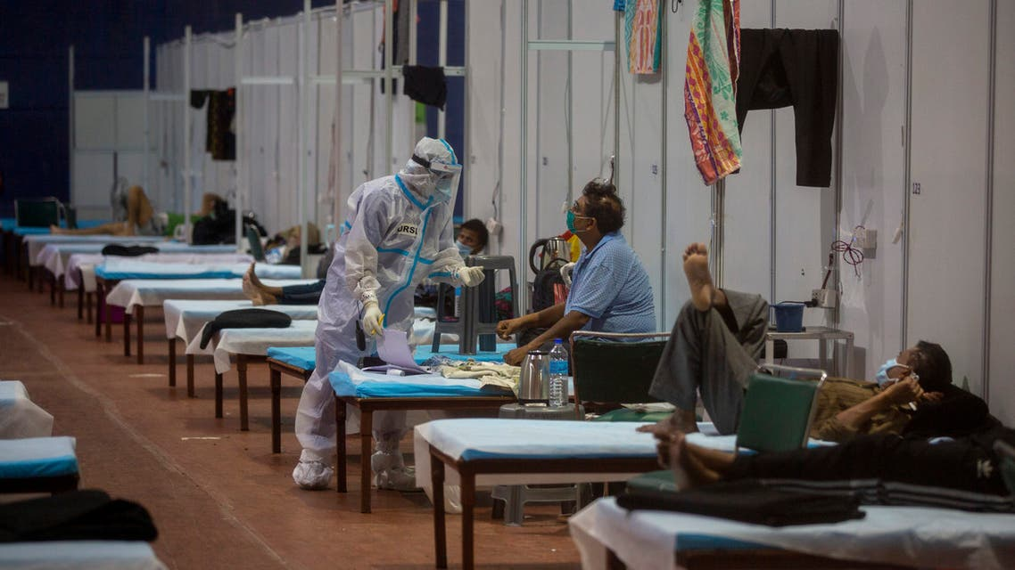 A health worker takes the temperature of a patient at a makeshift COVID-19 care center at an indoor sports stadium, in New Delhi. (AP)