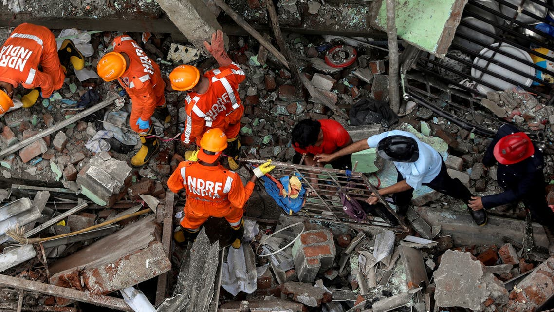 National Disaster Response Force (NDRF) officials and firemen remove debris as they look for survivors after a three-storey residential building collapsed in Bhiwandi on the outskirts of Mumbai, India. (Reuters)