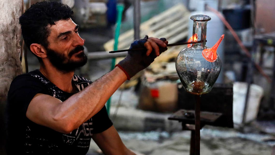A glassblower forms glass at factory, which is recycling the broken glass as a result of the Beirut explosion, in the northern Lebanese port city of Tripoli on August 25, 2020. (AFP)
