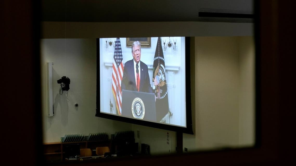 President Trump is seen on a screen through a window to an empty conference room as he delivers a pre-recorded address to the 75th annual UN General Assembly. (Reuters)