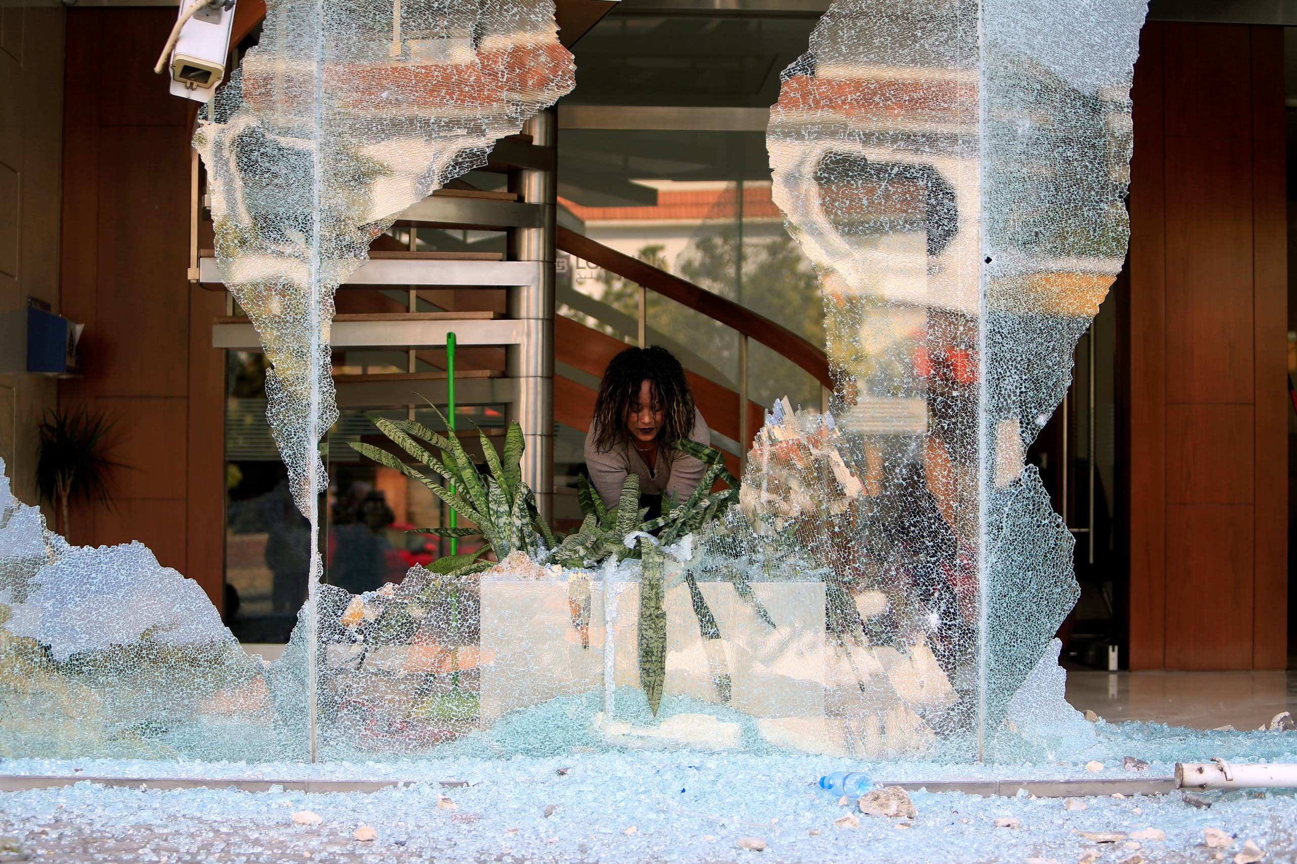 A worker cleans up broken glass from a bank facade after overnight protests against growing economic hardship in Sidon, Lebanon April 29, 2020. (Reuters)