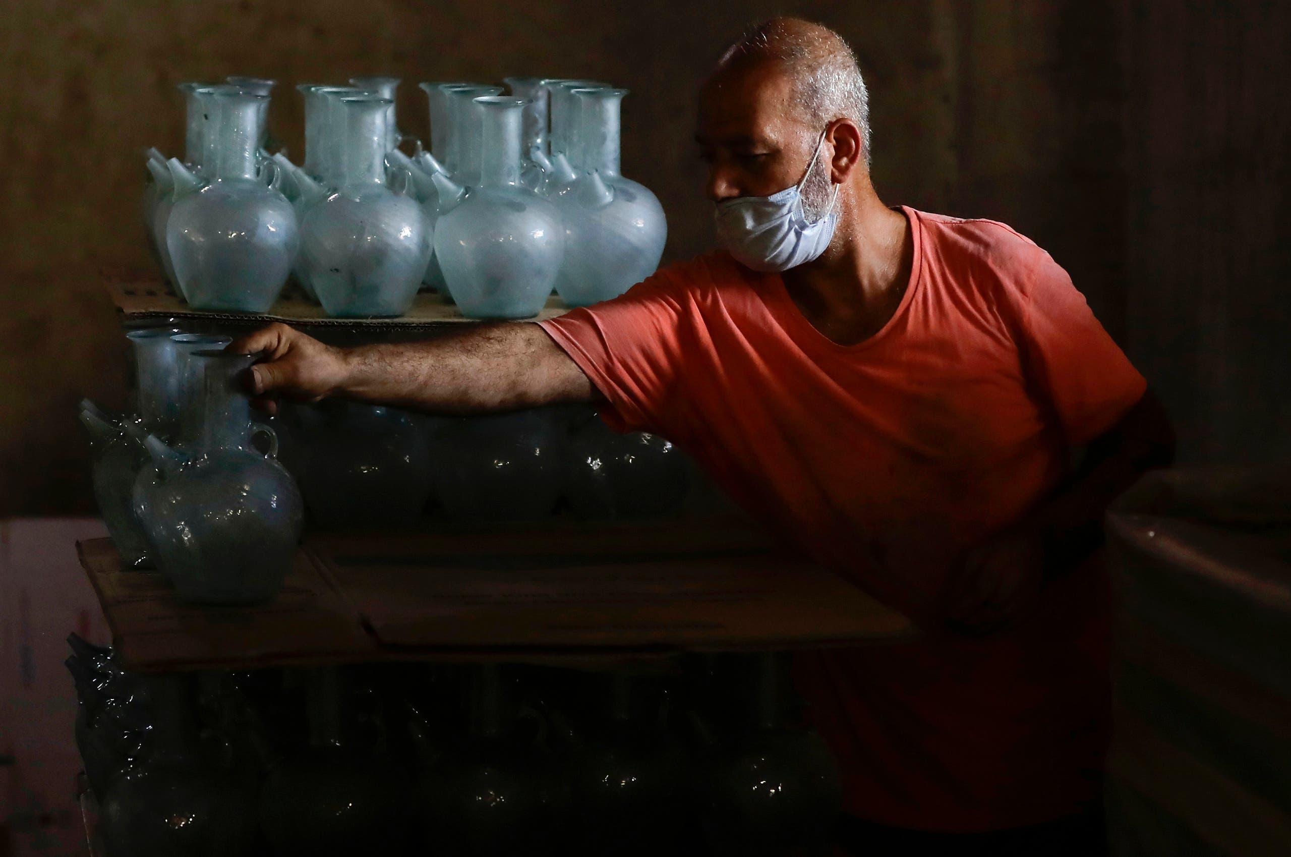A worker arranges finished jugs at a factory, which is recycling the broken glass as a result of the Beirut explosion, in the northern Lebanese port city of Tripoli on August 25, 2020. (AFP)