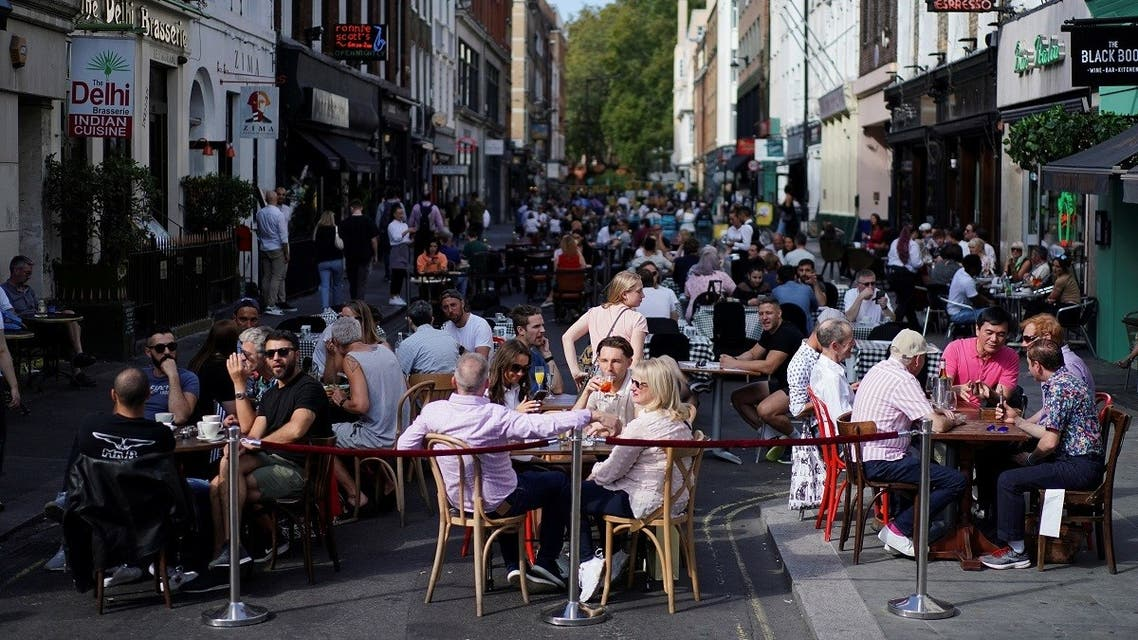 People sit at the tables outside restaurants in Soho, amid the coronavirus disease (COVID-19) outbreak, in London, Britain. (Reuters)