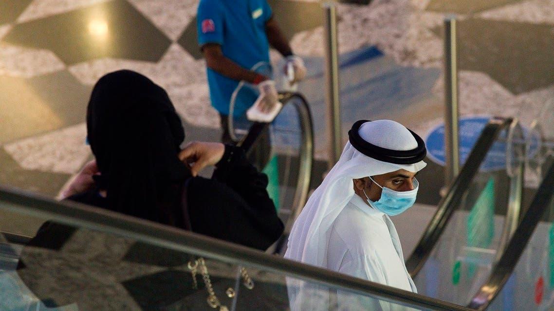 An Emirati man and woman ride an escalator at Mall of the Emirates in Dubai. (File photo: AP)