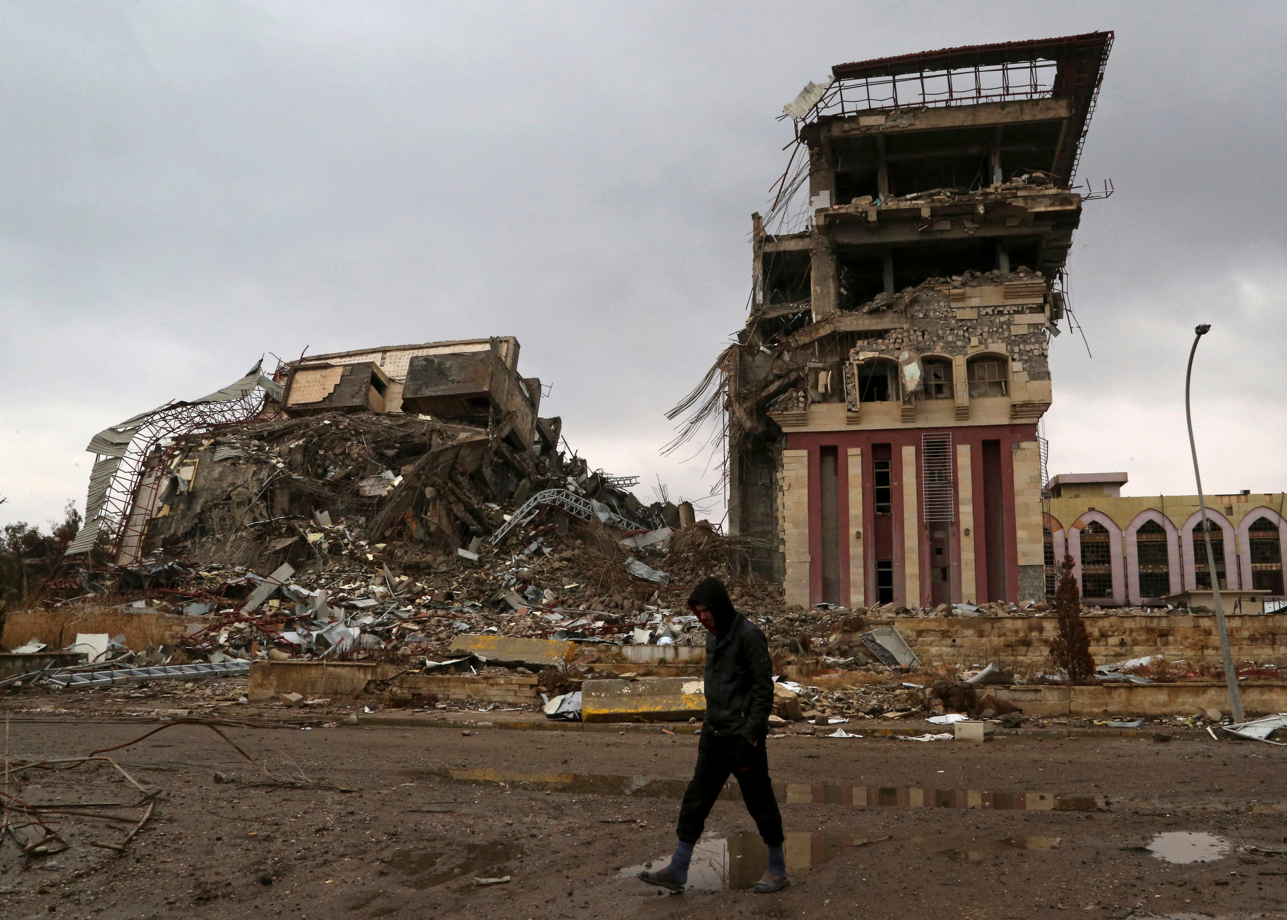 A student walks past badly damaged buildings at the University of Mosul, that was retaken by Iraqi security forces from Islamic State militants, on the eastern side of Mosul, Iraq, Sunday, Jan. 22, 2017. (AP)