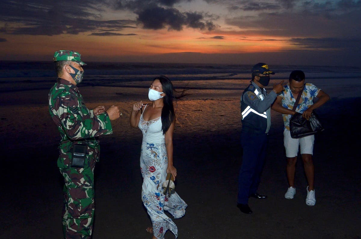 Officers wearing protective face masks give warning to visitors for wearing protective masks, amid the coronavirus disease (COVID-19) outbreak in Badung, Bali Province, Indonesia, on September 3, 2020. (Reuters)