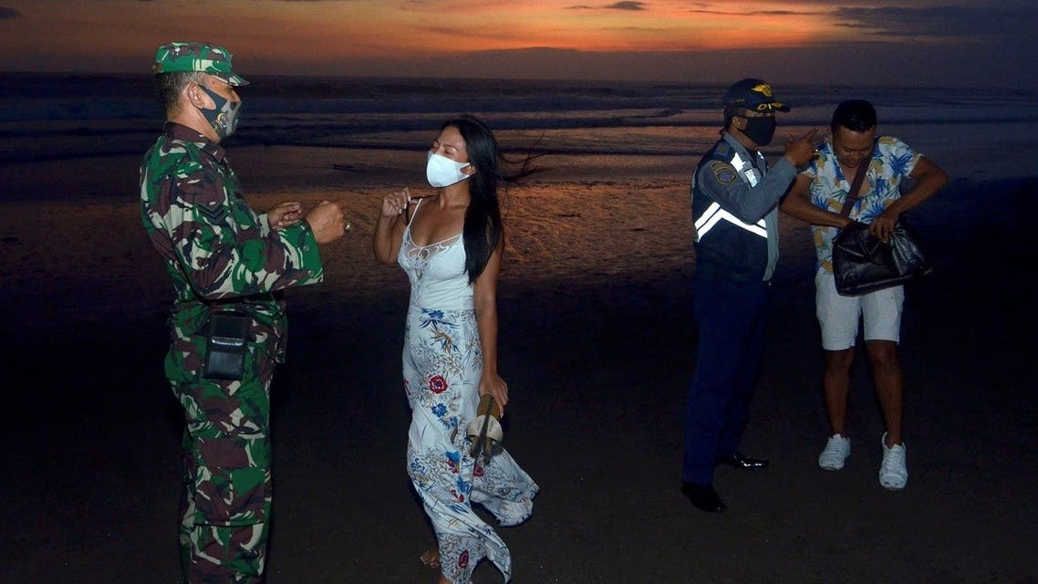 Officers wearing protective face masks give warning to visitors for wearing protective masks, amid the coronavirus disease (COVID-19) outbreak in Badung, Bali Province, Indonesia, on September 3, 2020. (Reuters) _1719615014_RC22UI9DONXJ_RTRMADP_3_HEALTH-CORONAVIRUS-INDONESIA-BALI