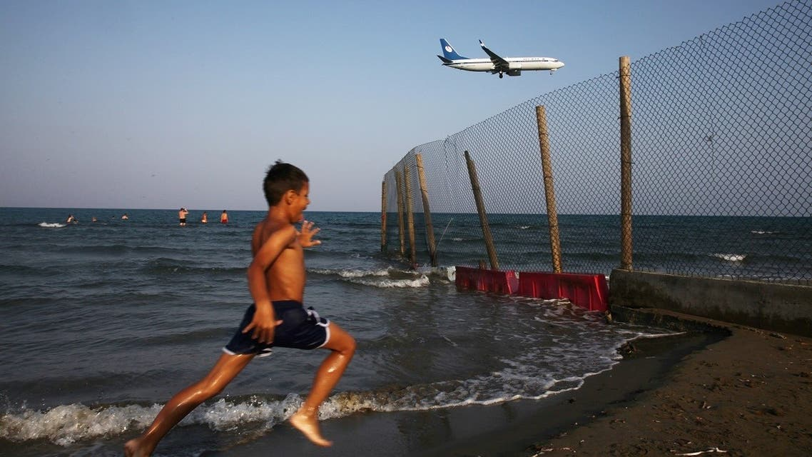 A boy runs on a beach while an airplane prepares to land at Larnaca International Airport, Cyprus. (File photo: Reuters)