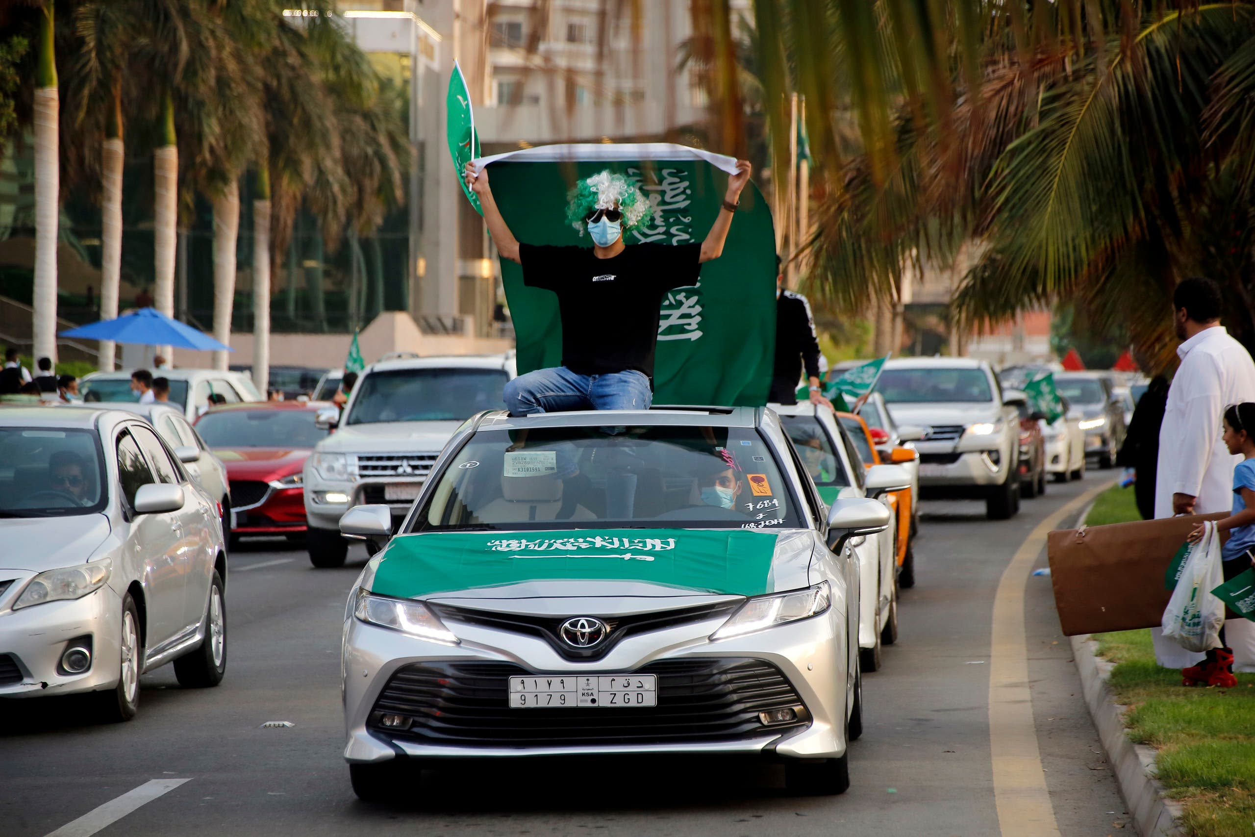 A Saudi waves a national flag as he wears a face mask to protect against coronavirus during celebrations marking National Day to commemorate the unification of the country as the Kingdom of Saudi Arabia, in Jeddah, Saudi Arabia, Wednesday, Sept. 23, 2020. (AP)