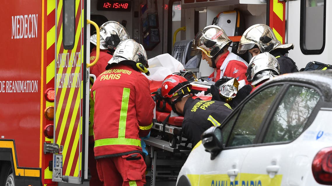 French firefighters load an injured person into a waiting ambulance near the former offices of the French satirical magazine Charlie Hebdo. (AFP)