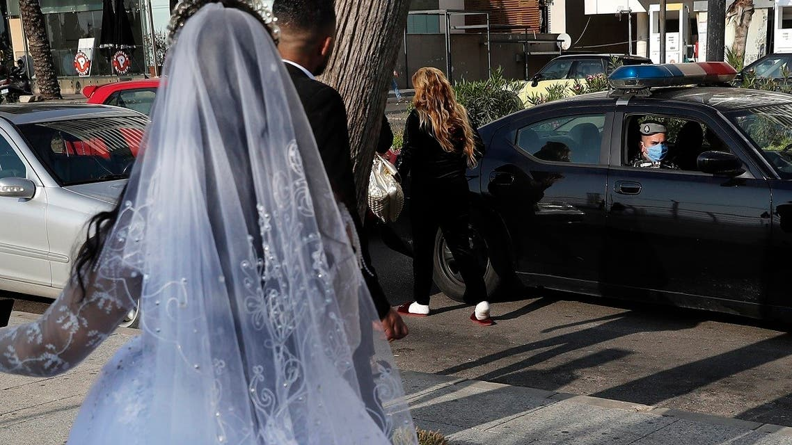 A policeman asks a bride and groom to leave the waterfront promenade where they had decided to take some pictures, in Beirut, Lebanon. (File Photo: AP)
