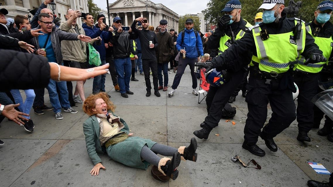 A woman gestures after falling as police move in to disperse protesters demonstrating against coronavirus restrictions in Trafalgar Square in London on September 26, 2020. (AFP)