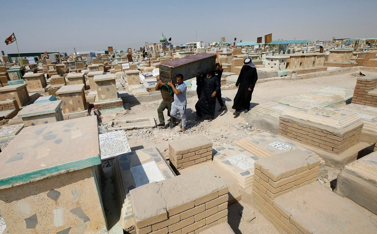 Iraqi men carry the coffin of a relative who, according to them, died of the coronavirus disease (COVID-19), after being taken from a cemetery dedicated to those who died of COVID-19, as they arrive to rebury him at the Valley of Peace cemetery located in the holy city of Najaf, Iraq. (Reuters)