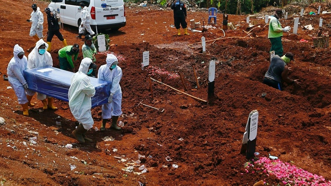 Workers wearing protective suits carry a coffin at the Muslim burial area provided by the government for victims of the coronavirus disease (COVID-19) at Pondok Ranggon cemetery complex in Jakarta, Indonesia. (Reuters)