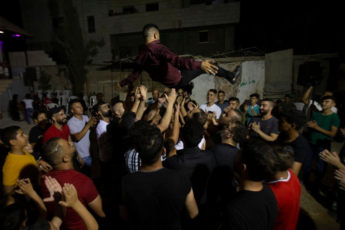 A Palestinian groom is thrown in the air during a wedding party in Azmut near the West Bank city of Nablus, Sept. 24, 2020. (AP)
