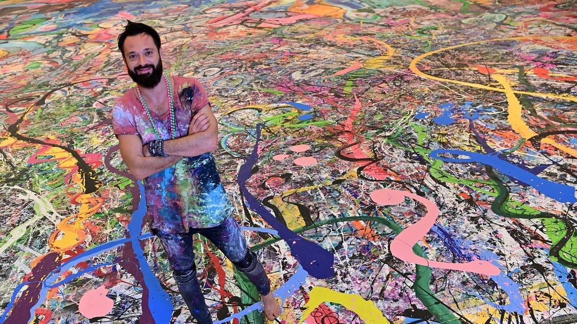 Contemporary British artist Sacha Jafri stands on his record-breaking painting entitled 'The Journey of Humanity'. (AFP)