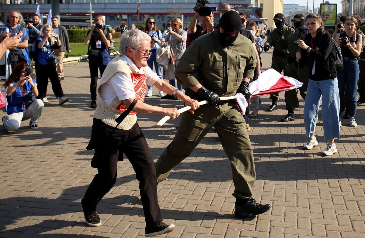 A law enforcement officer tries to take away a former white-red-white flag of Belarus from opposition activist Nina Baginskaya,73, during a rally in Minsk, September 26, 2020. (AFP)