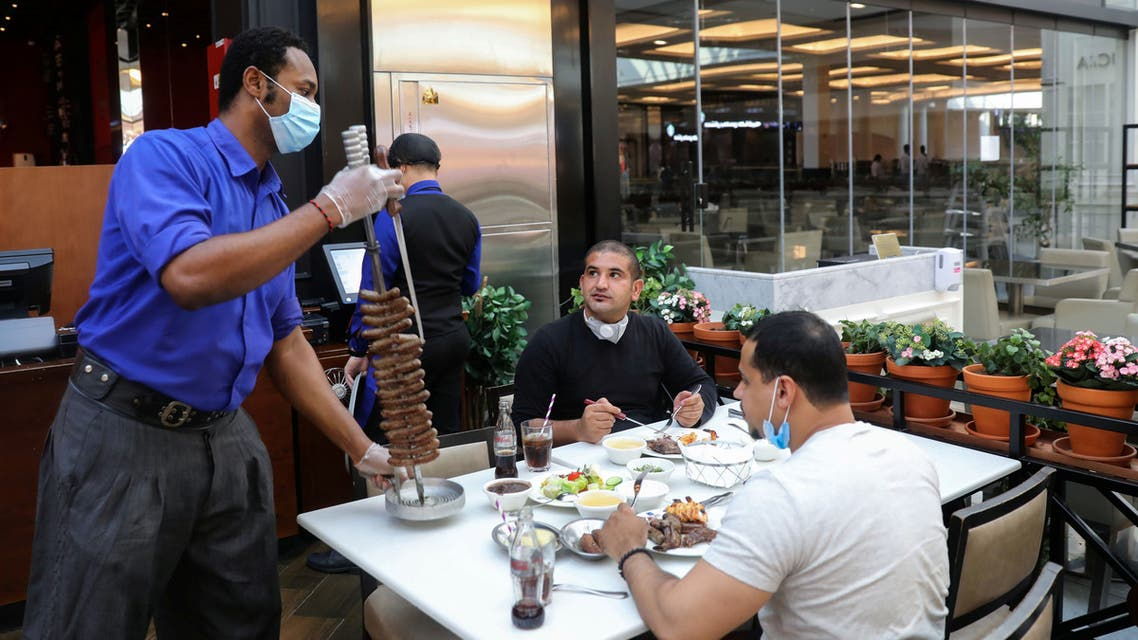 A worker wearing a protective face mask and gloves serves food at a restaurant during the reopening of malls, following the outbreak of the coronavirus disease (COVID-19), at Mall of the Emirates in Dubai. (Reuters)