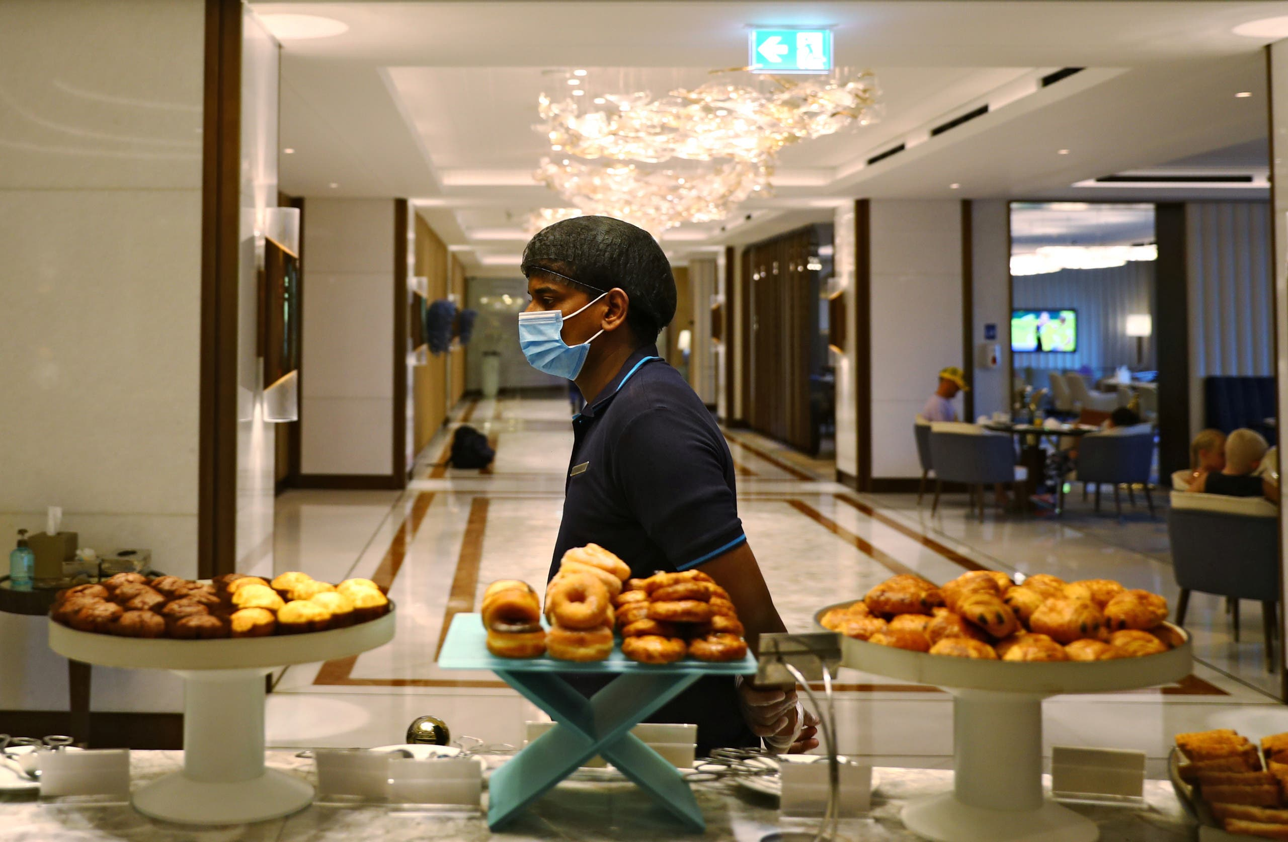 A waiter wearing a face mask walks past a buffet in the Atlantis The Palm hotel in Dubai. (File photo: Reuters)