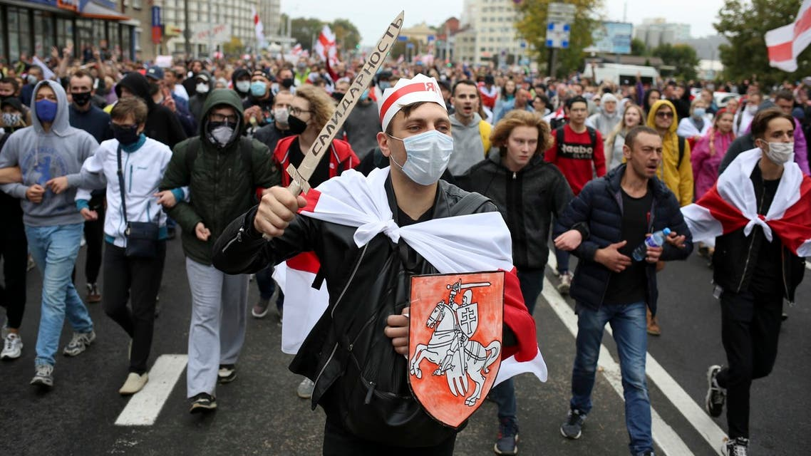 Demonstrators, one of them wearing an old Belarusian nation flag and holding a cardboard sword reading solidarity march during an opposition rally to protest the official presidential election results in Minsk, Belarus, Sunday, Sept. 27, 2020. (AP)