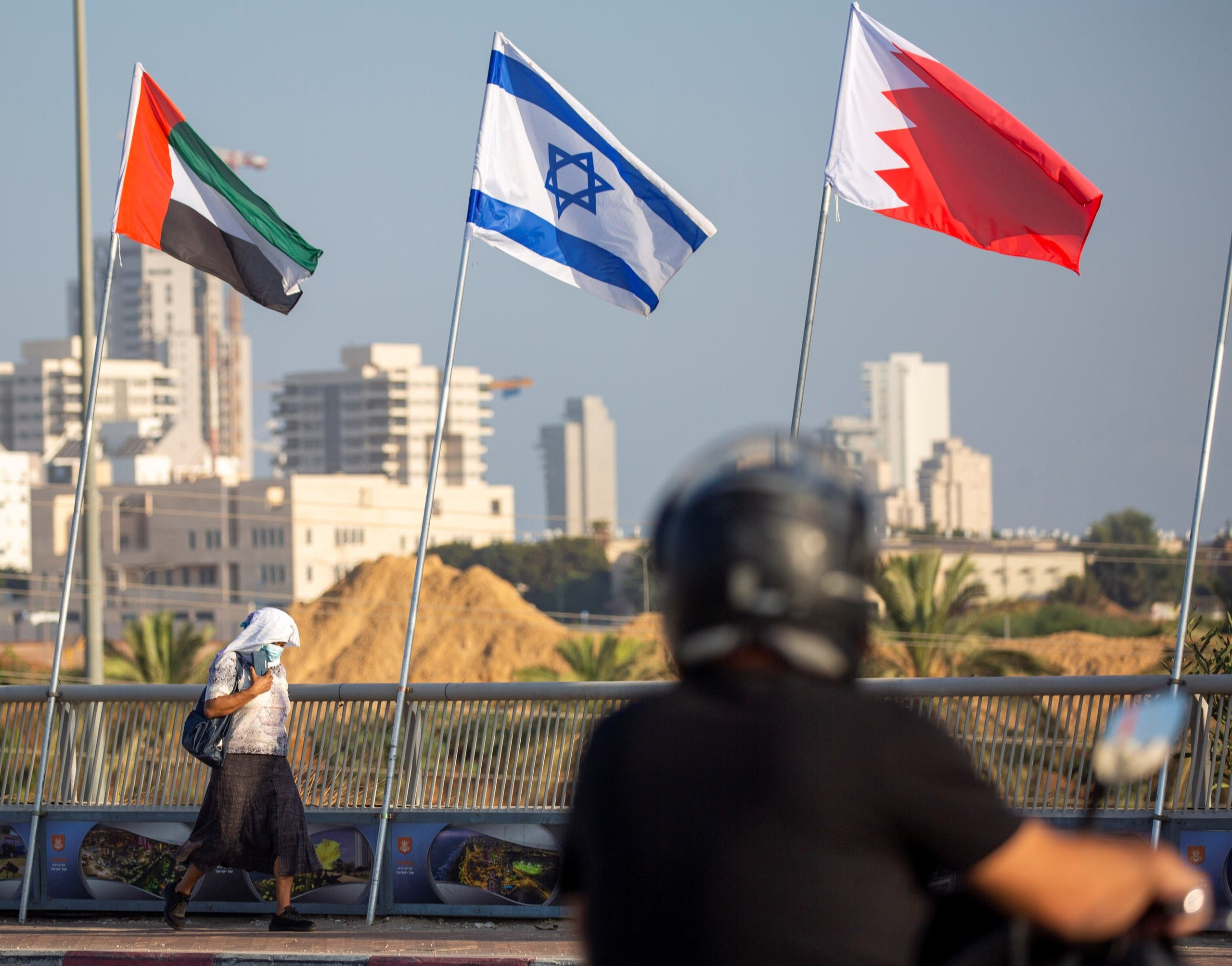 A woman wearing a face mask against the coronavirus pandemic walks past United Arab Emirates, Israel and Bahraini flags in Netanya, Israel on Sept. 14, 2020. (AP)