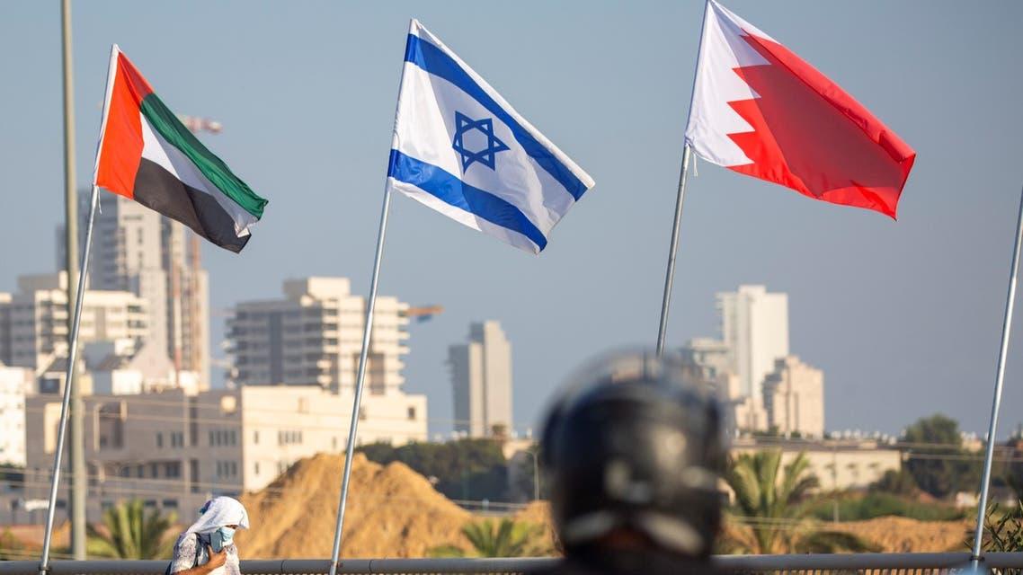 A woman wearing a face mask against the coronavirus pandemic walks past United Arab Emirates, Israel and Bahraini flags in Netanya, Israel on Sept. 14, 2020. (AP)