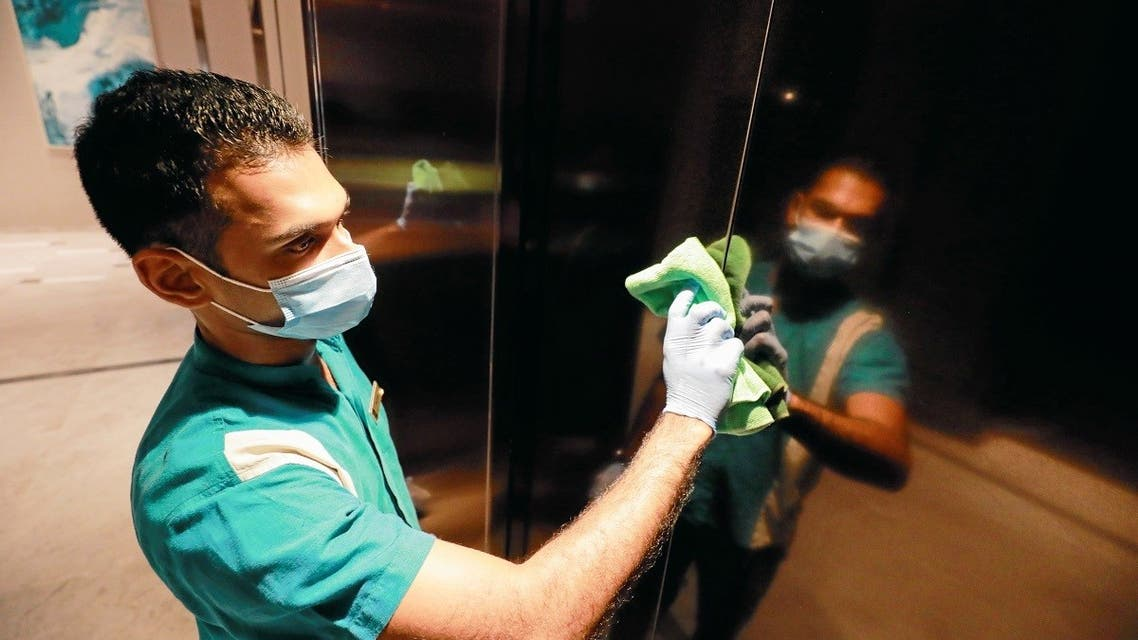 A cleaner wearing a protective mask cleans the elevator doors at the Shangri-La hotel, in Colombo. (Reuters)