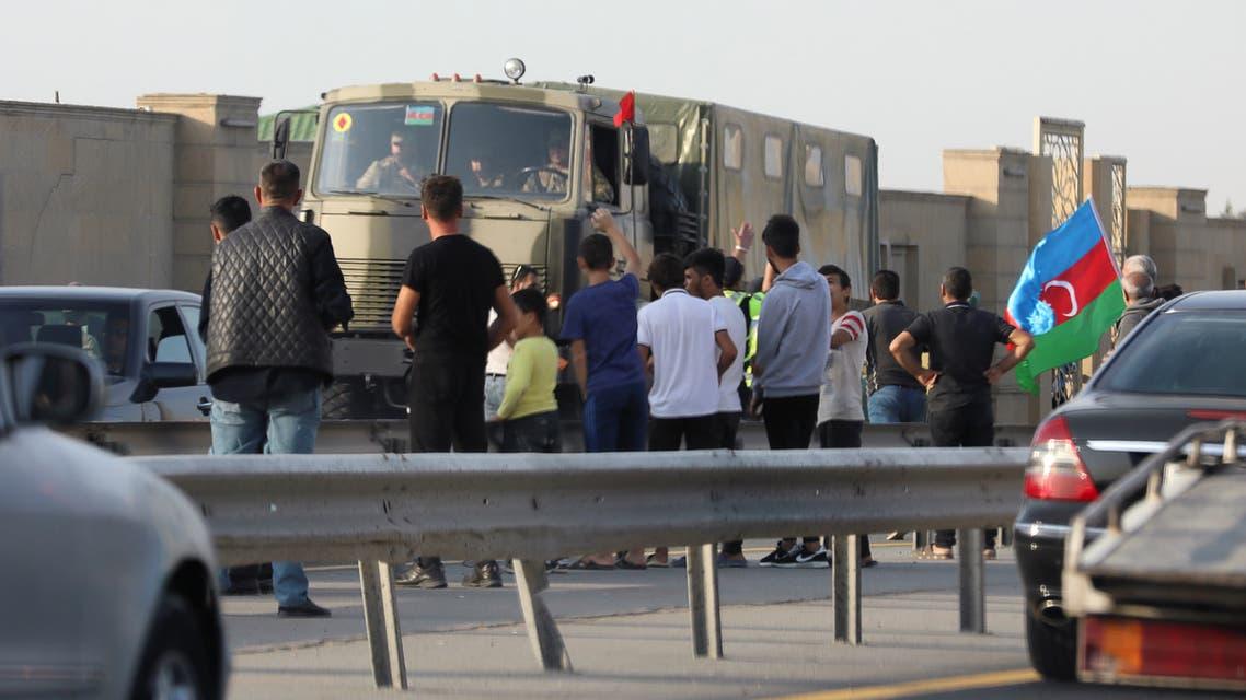 People line up along the roadside to greet Azerbaijani service members, who drive a truck in Baku, Azerbaijan September 27, 2020. (Reuters)