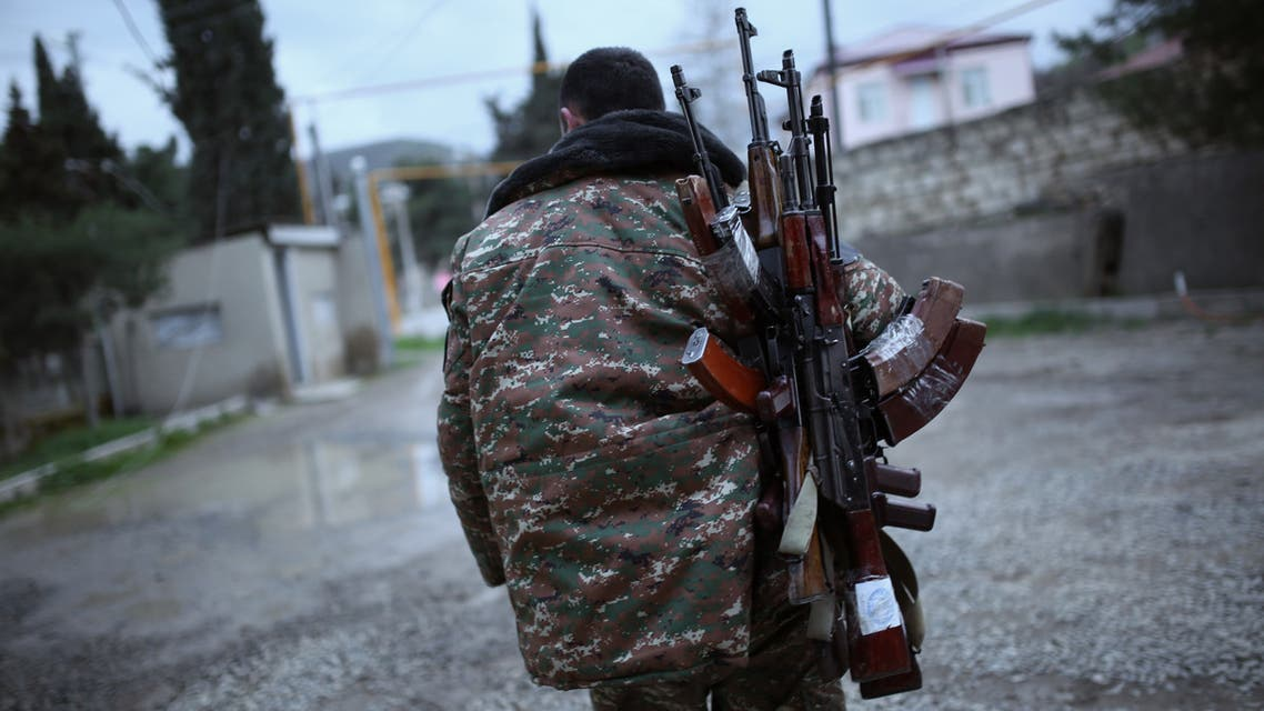 A soldier of the self-defense army of Nagorno-Karabakh carries weapons in Martakert region on April 4, 2016. AFP