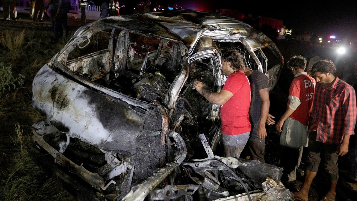 Rescue workers examine a burnt van at the accident site outside of Karachi, Pakistan. (AP)