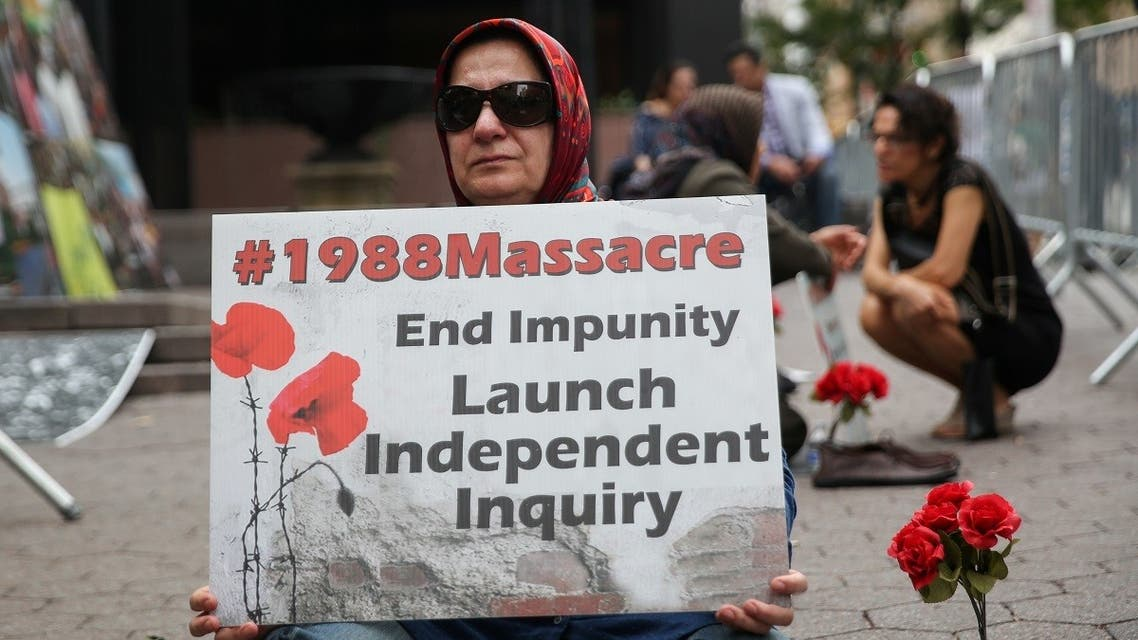 A woman holds a poster that reads 1988 Massacre. End Impunity Launch Independent Inquiry as she attends a protest against Iranian President Hassan Rouhani outside of U.N. headquarters. (Reuters)